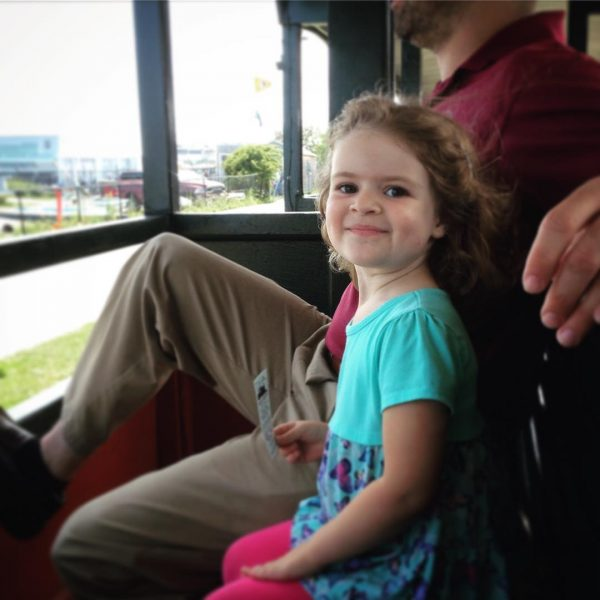 happy little girl on a train at the Maine Narrow Gauge Railroad
