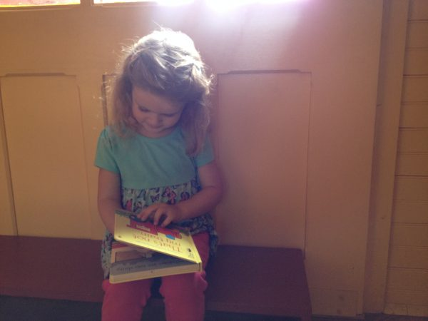 little girl reading in a railroad car