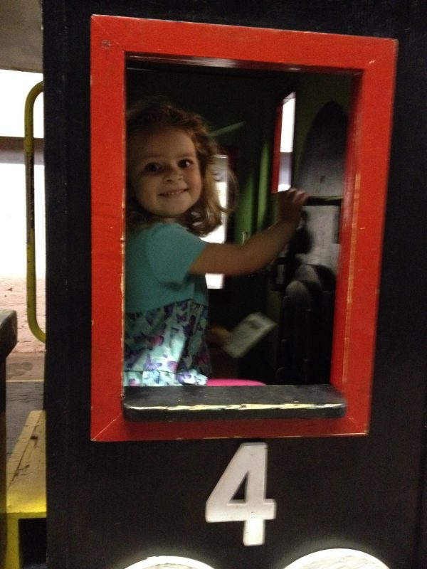 little girl on toy railcar