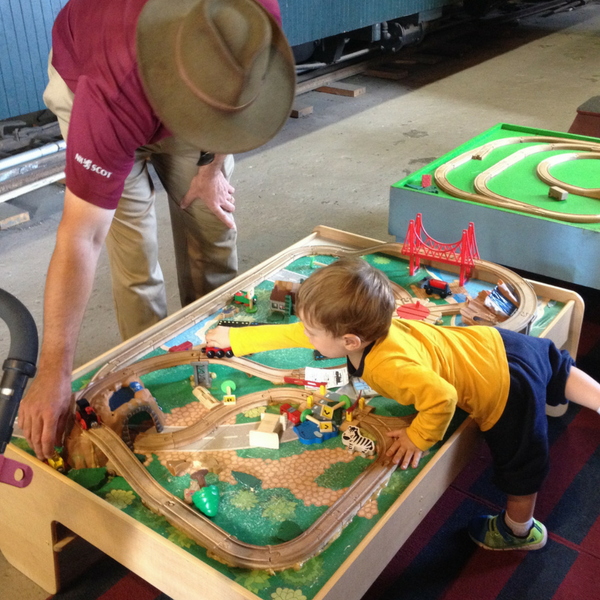 little boy playing trains with father